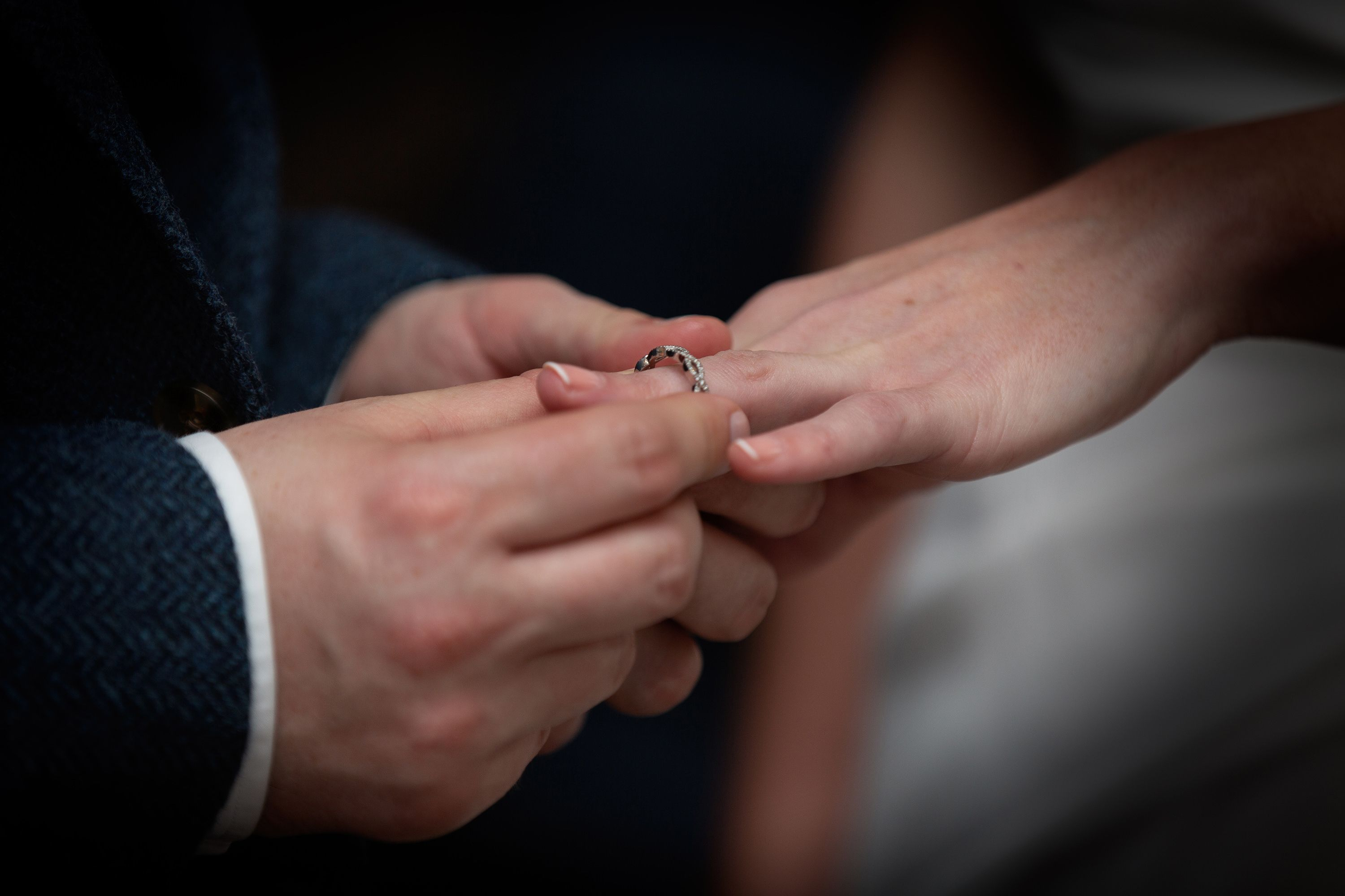 the brides wedding ring being placed on her finger