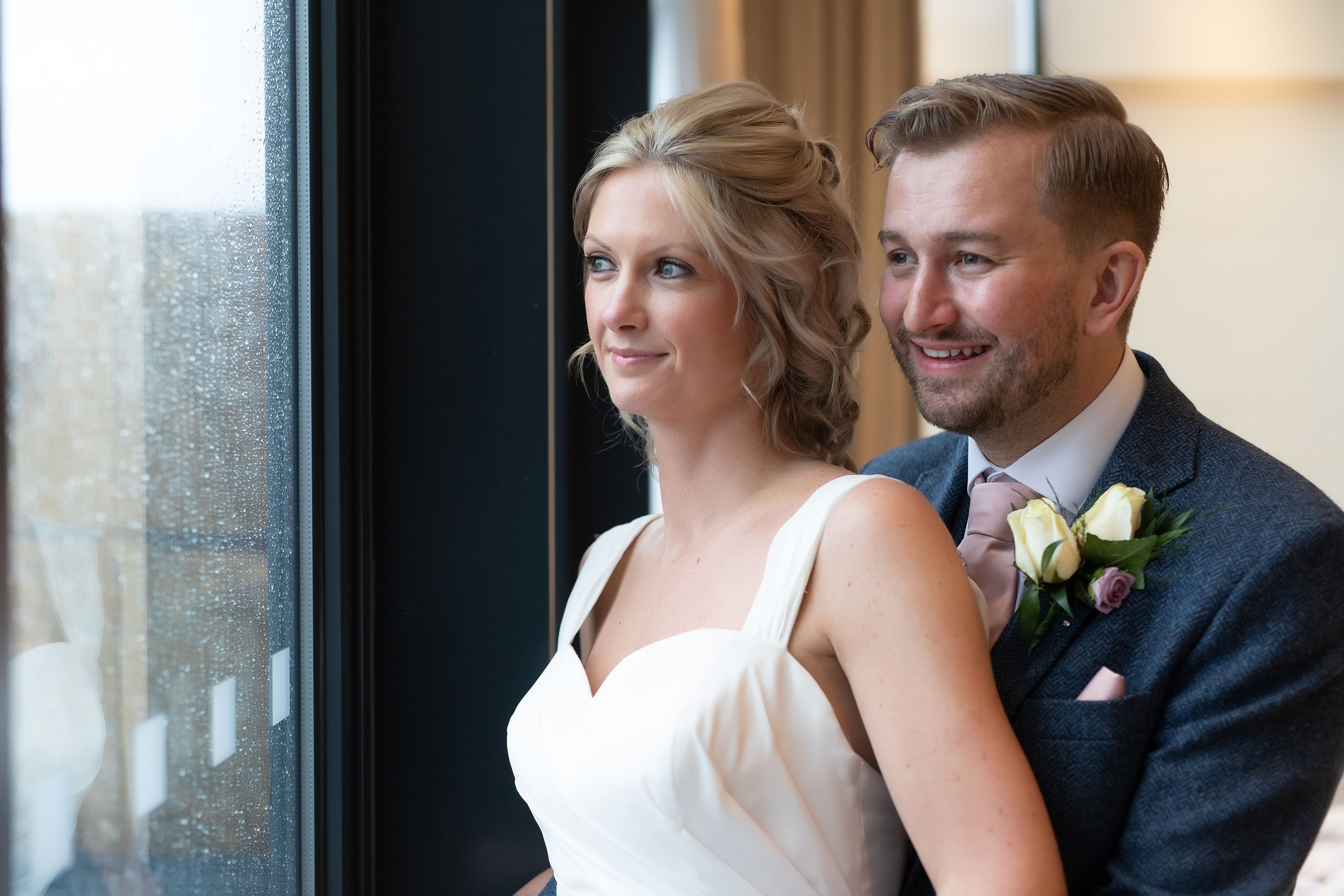 the bride and groom look out the top window at the Hope street hotel hotel in Liverpool