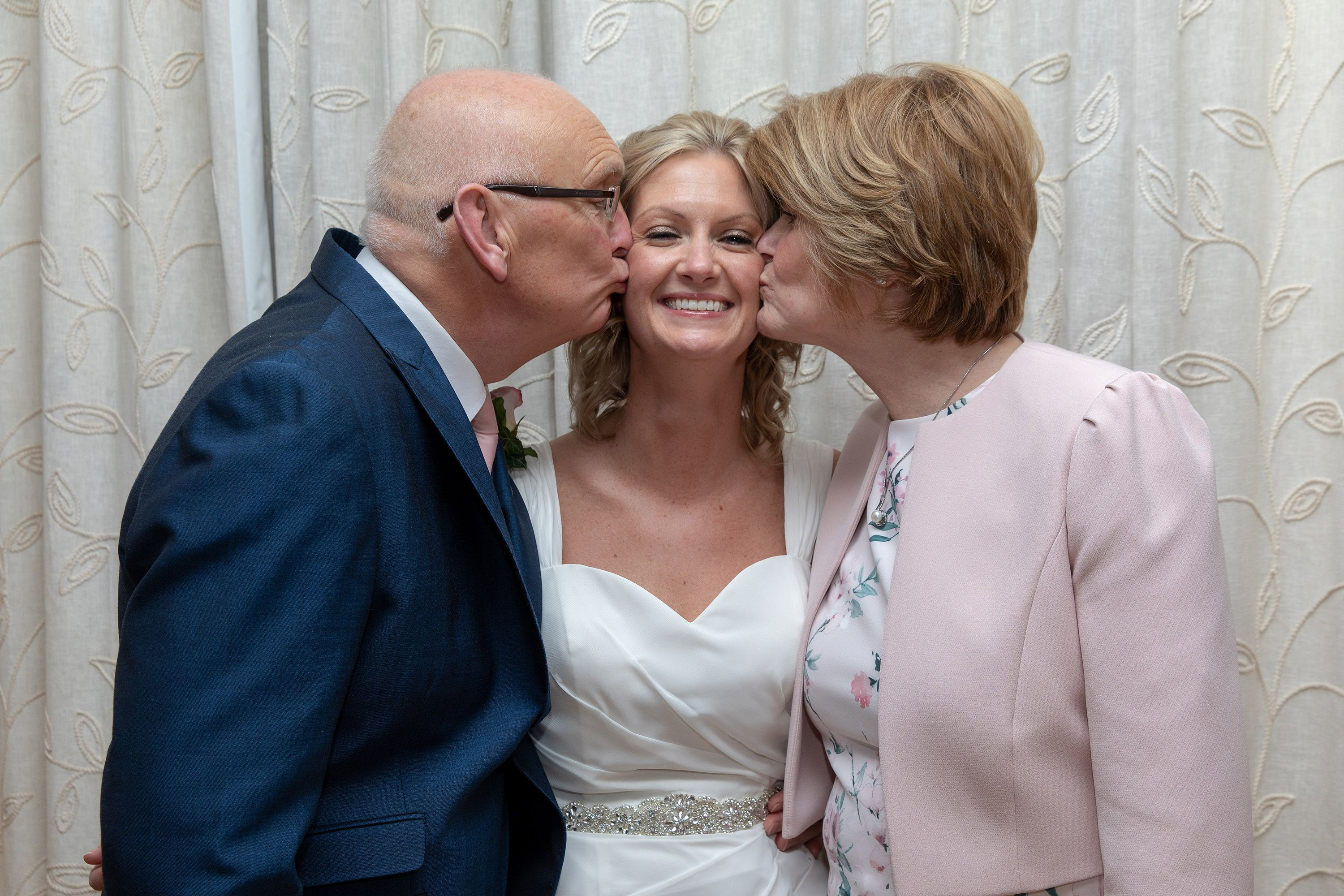 mother and father of the bride and groom give her a kiss