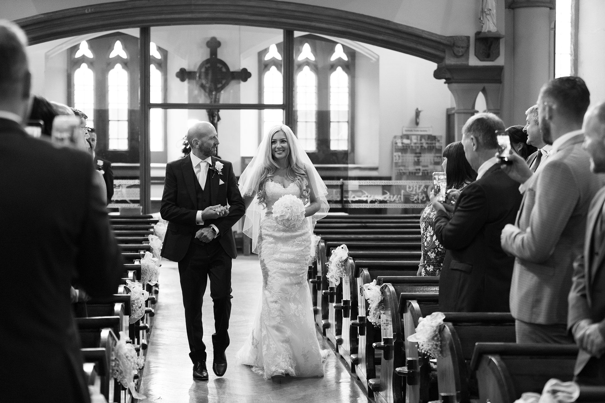 the father of the bride walks down the aisle with his daughter