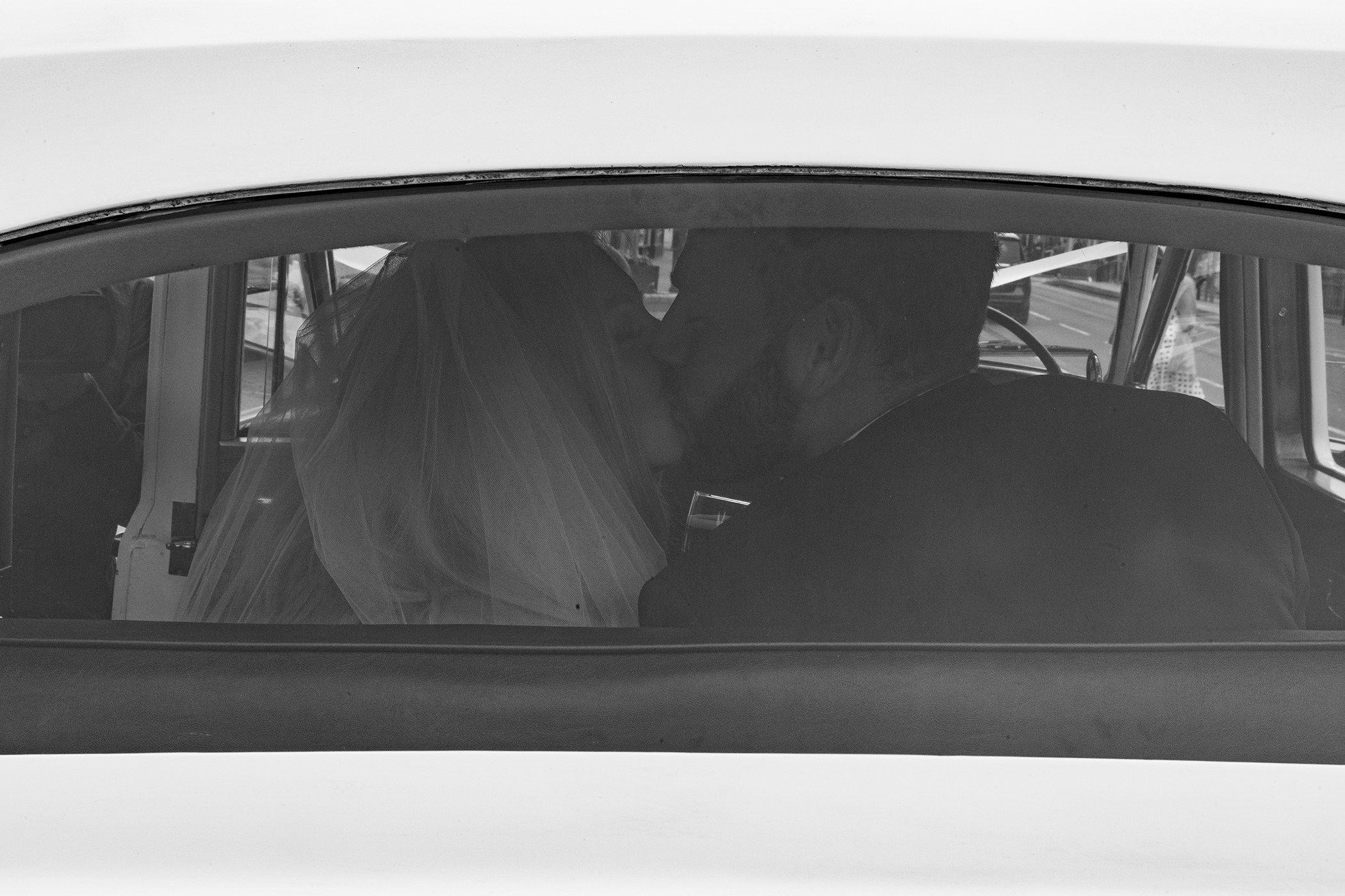 bride and groom kiss in the back of the wedding car