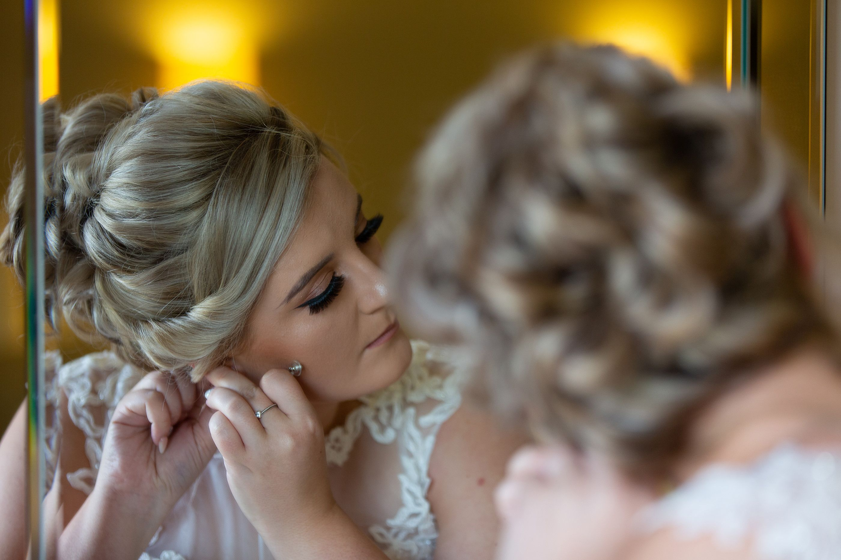 the bride putting earrings on