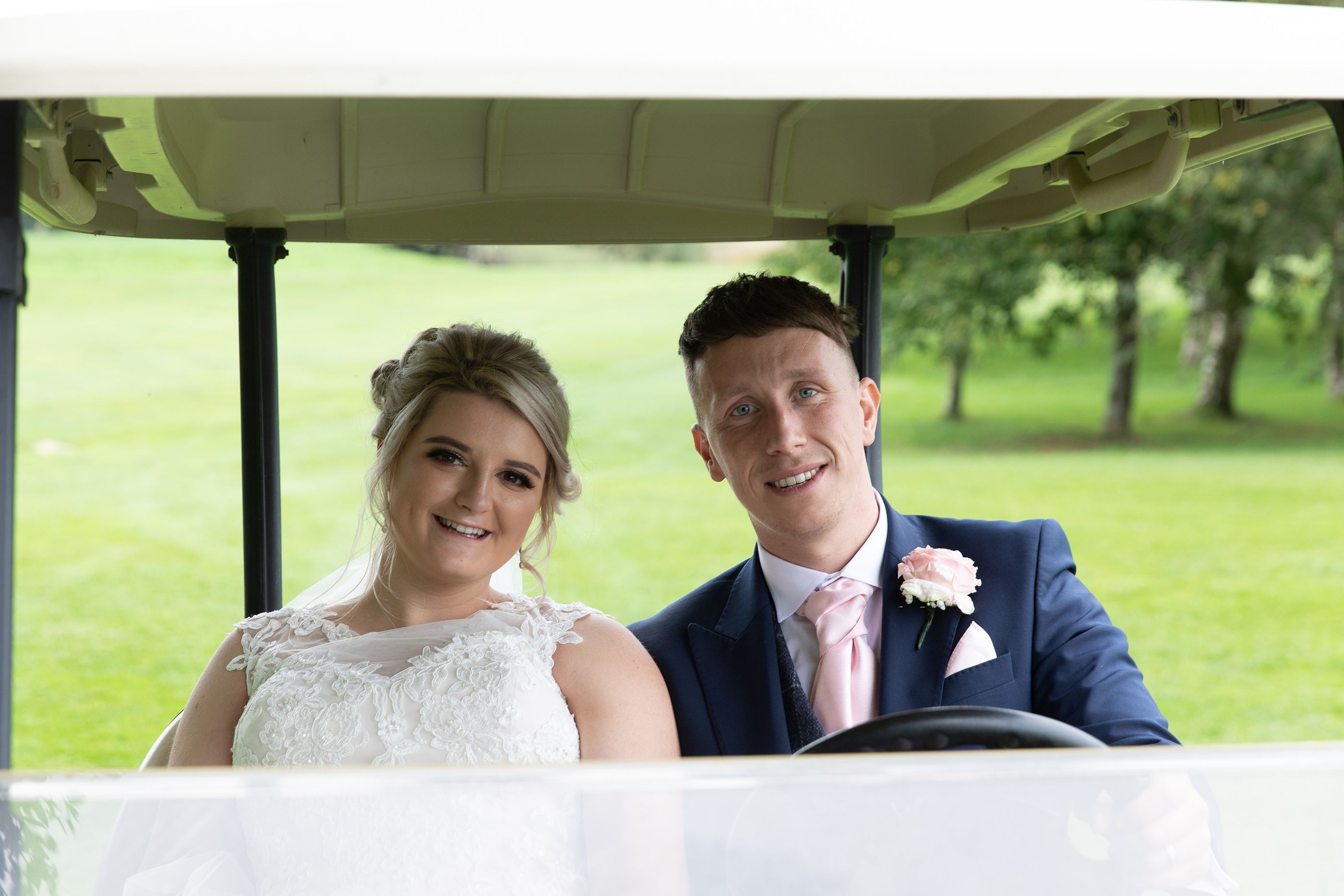 the bride and groom in the golf buggy