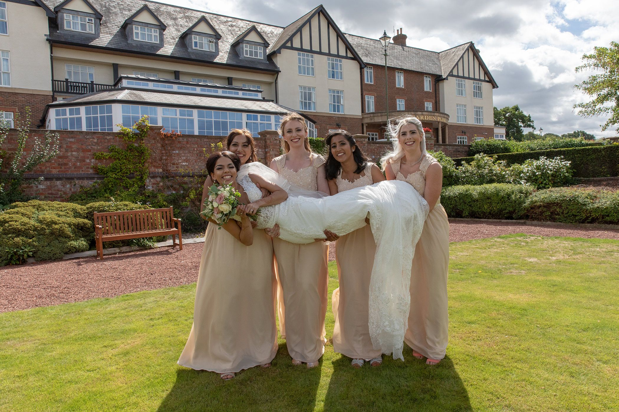 bride and bridesmaids carrying her