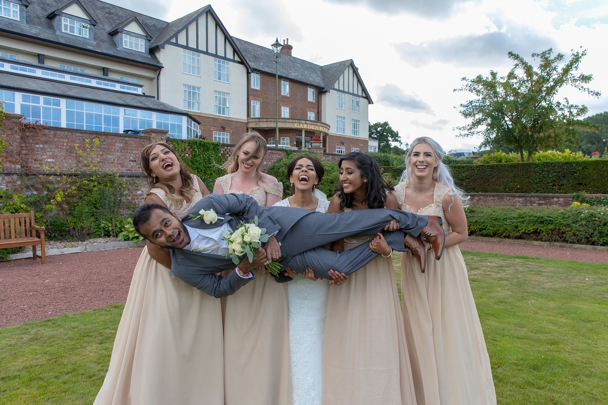 groom and bridesmaids carrying him