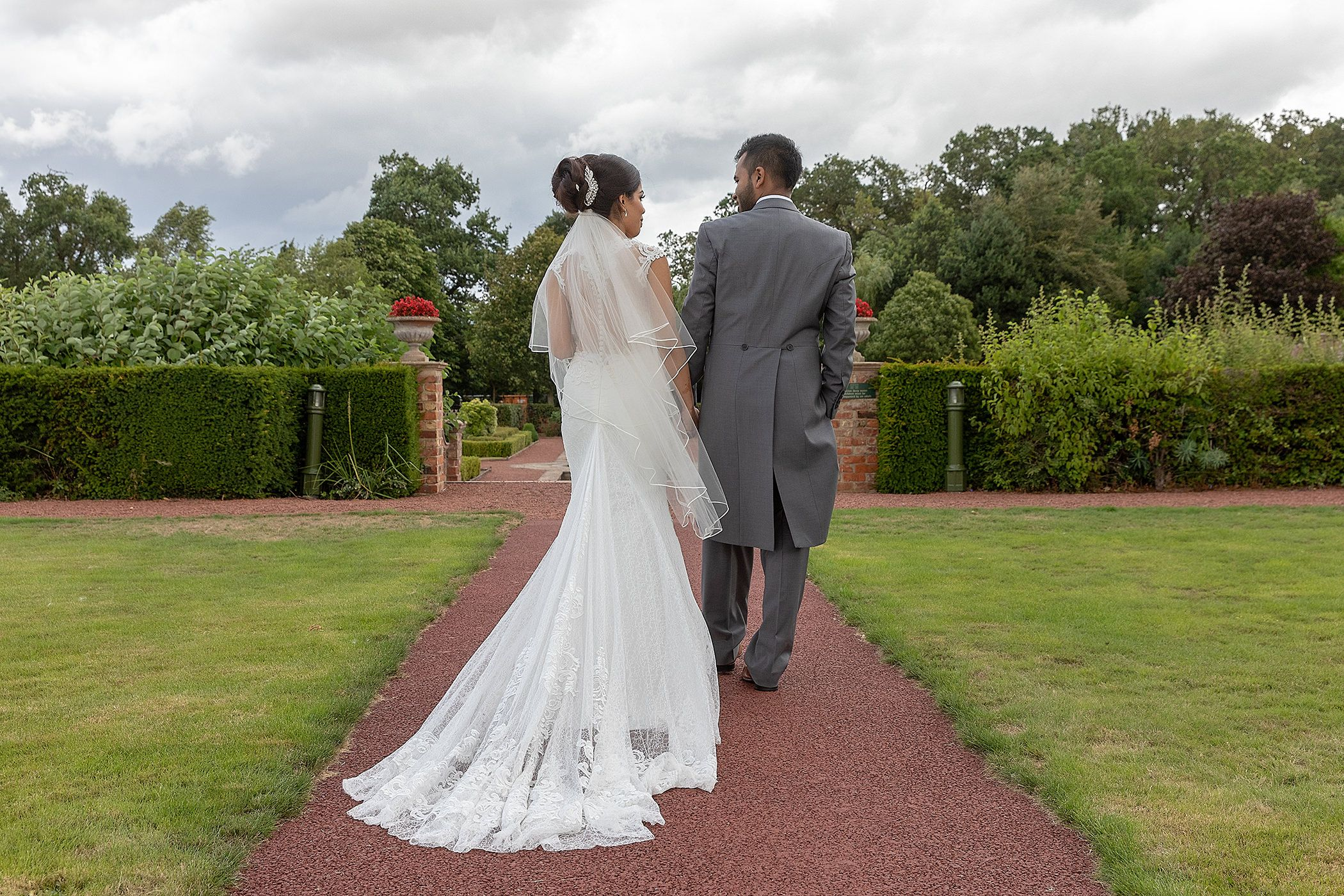 bride and groom walk through the gardens