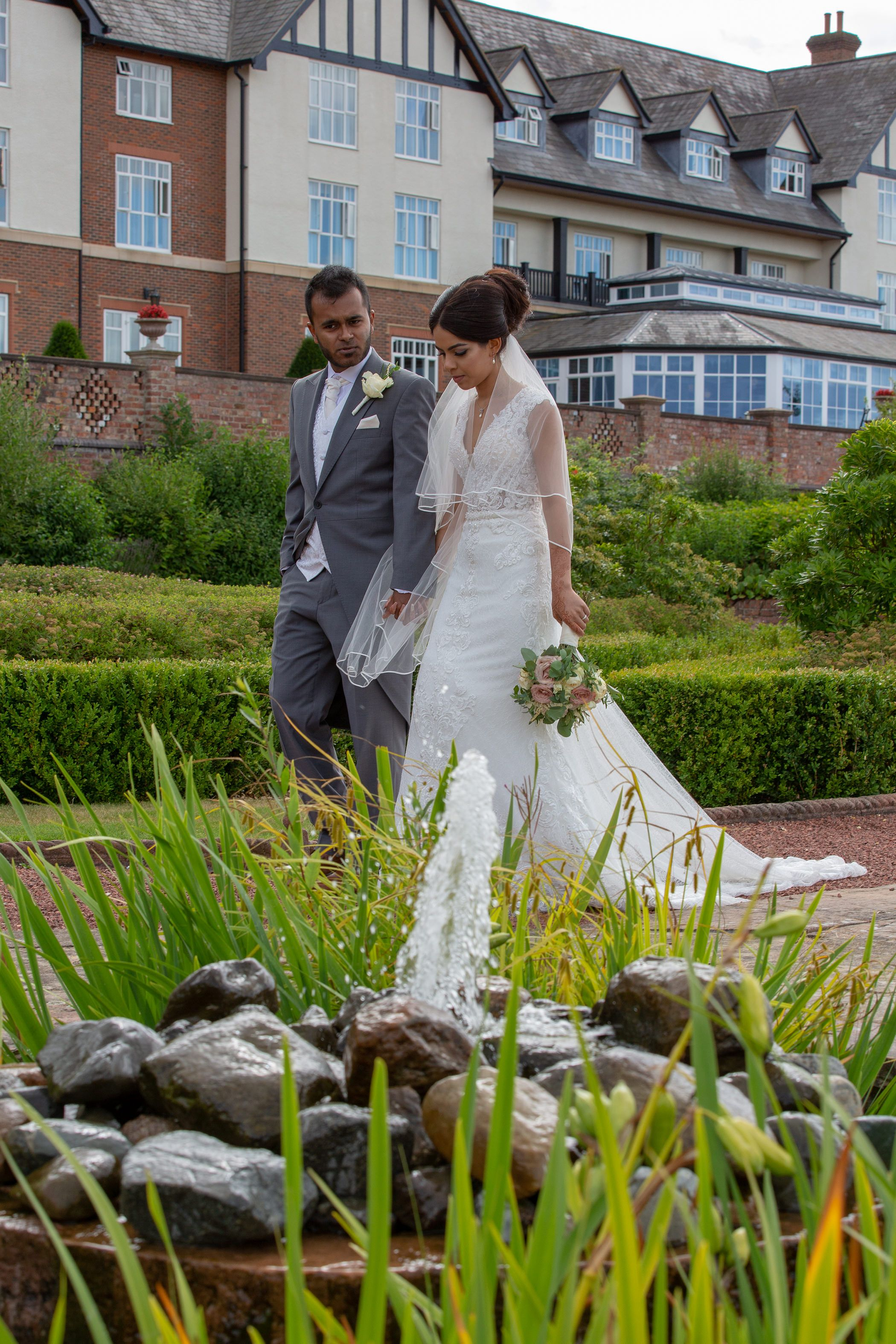 bride and groom in the gardens at Carden Park Hotel