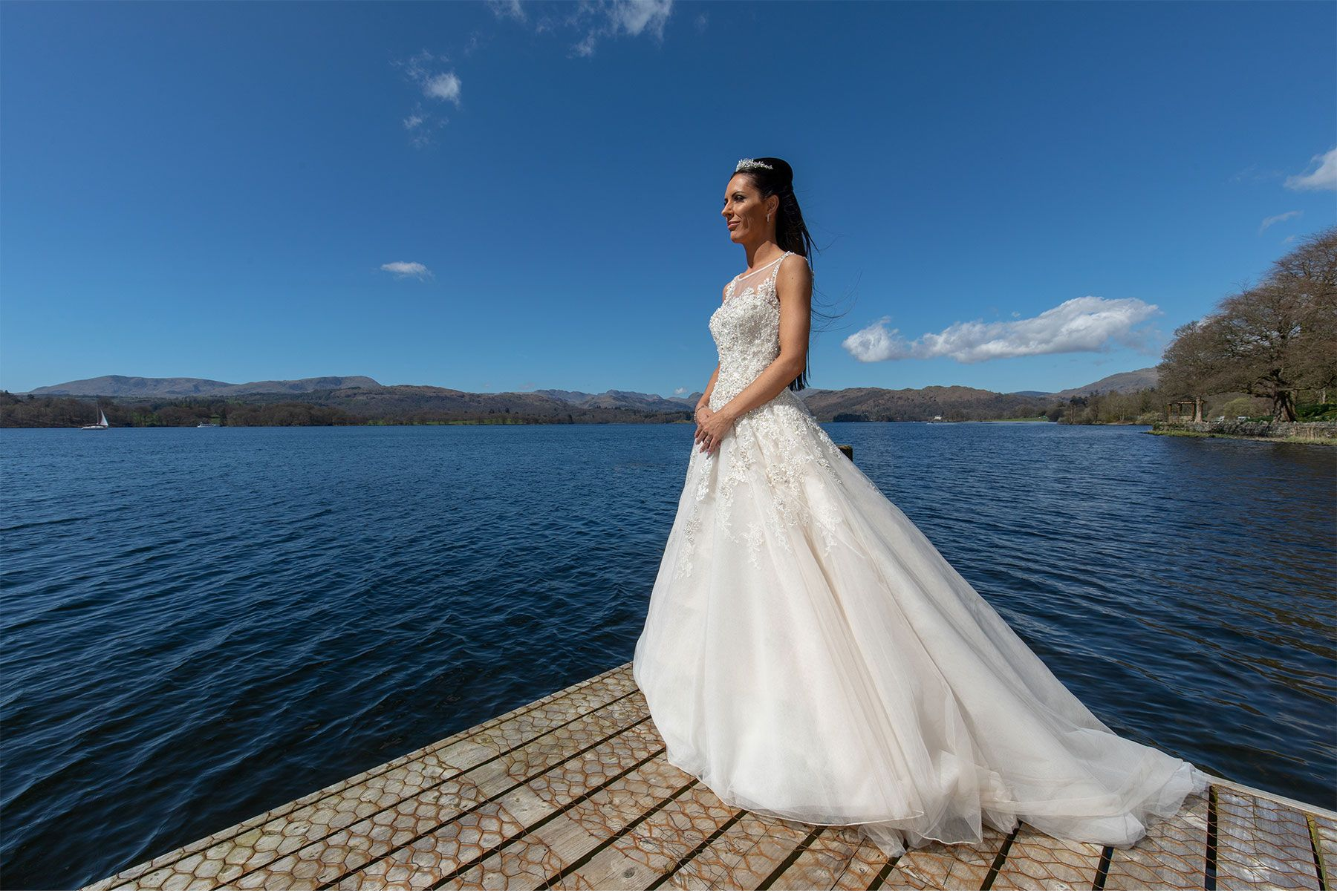 The bride set against lovely blue sky on the jetty of Lake Windermere