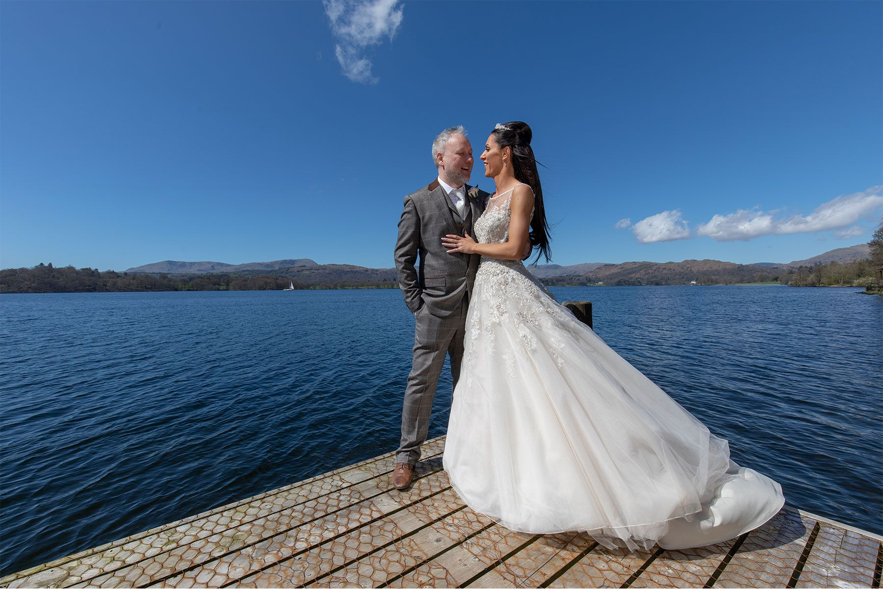 The bride and groom set against lovely blue sky on the jetty of Lake Windermere