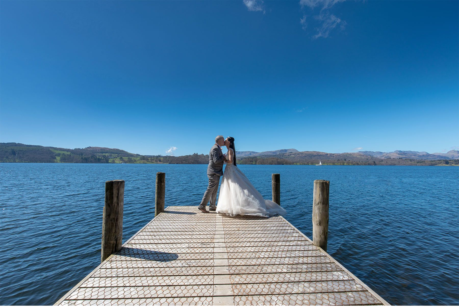The bride and groom set against lovely blue sky on Lake Windermere