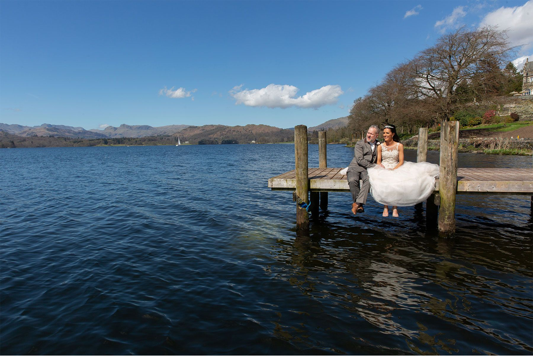 The bride and groom sat on the jetty  on Lake Windermere