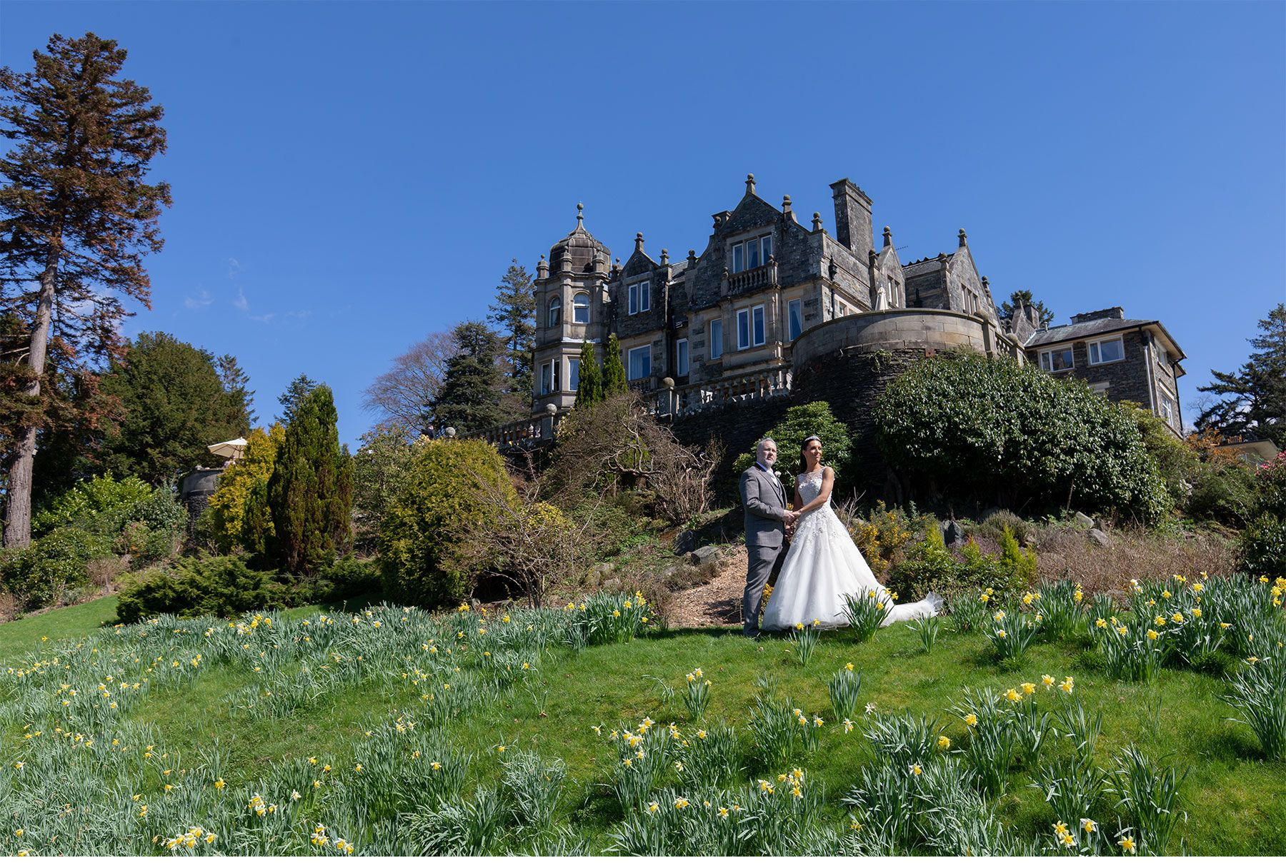 The bride and groom below the wonderful building of the Langdale Chase Hotel