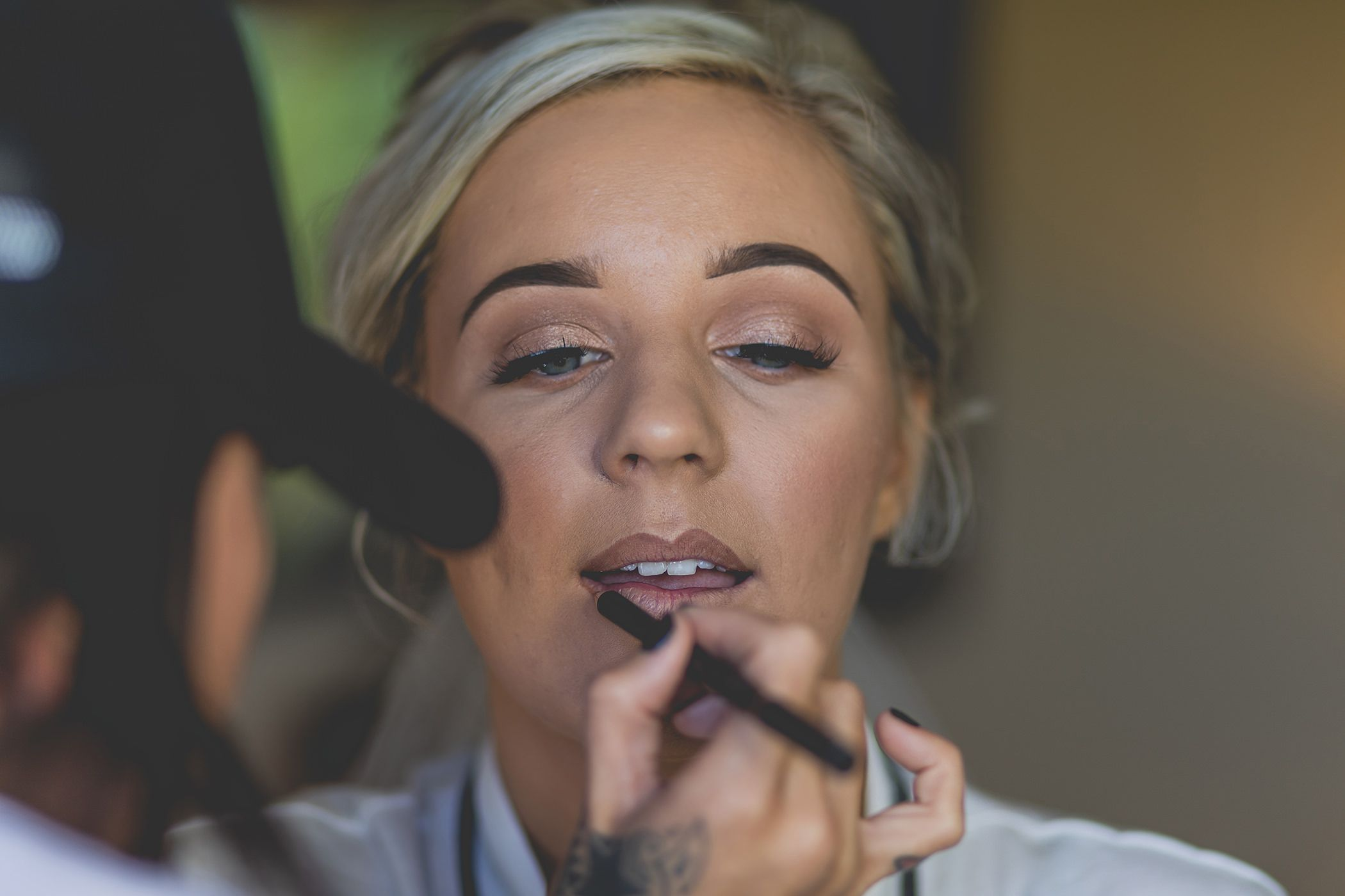 bride getting her lips painted