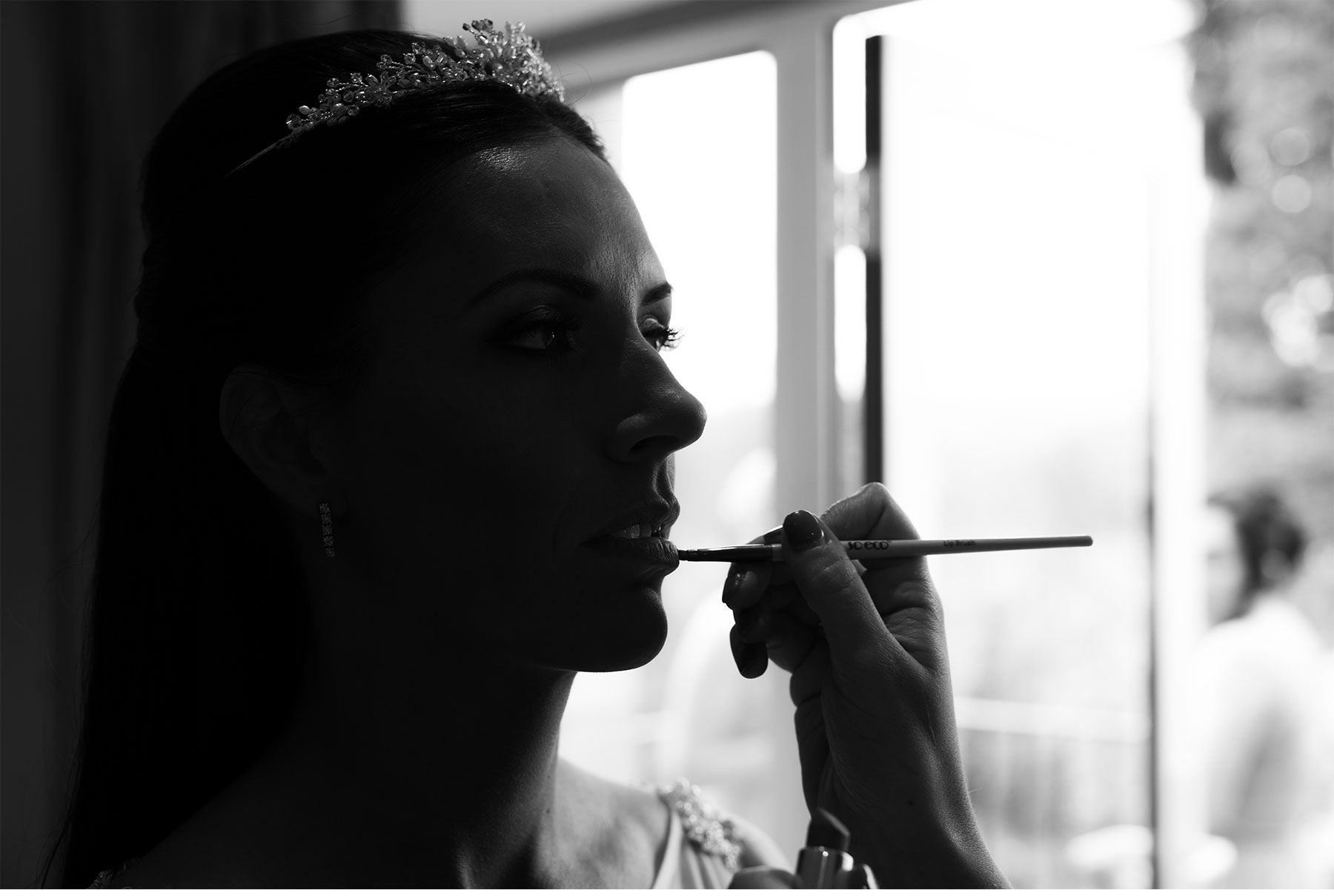 Bride having final touches done to her makeup