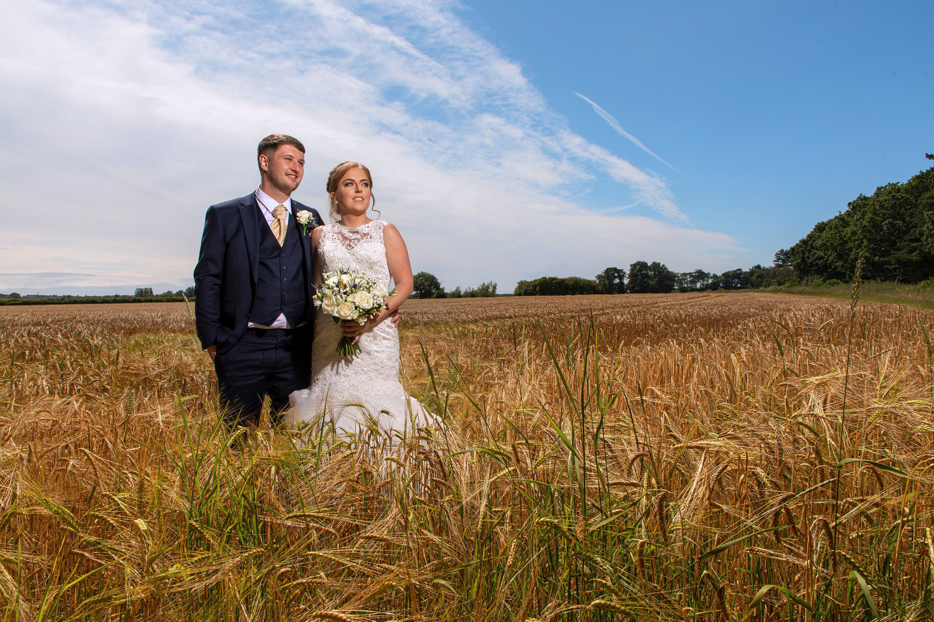 the bride and groom in a wheat field