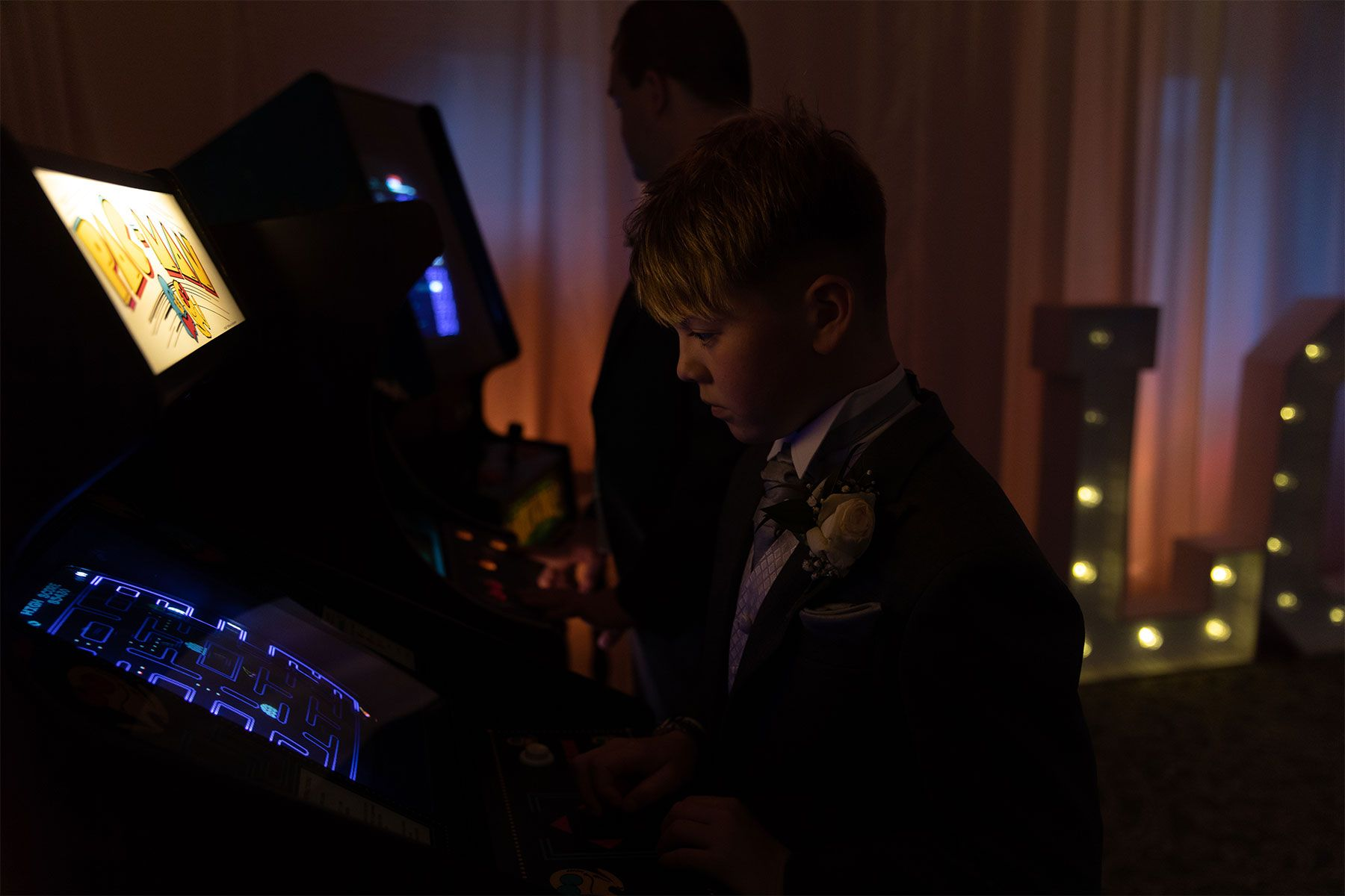 wedding guests having fun with arcade games