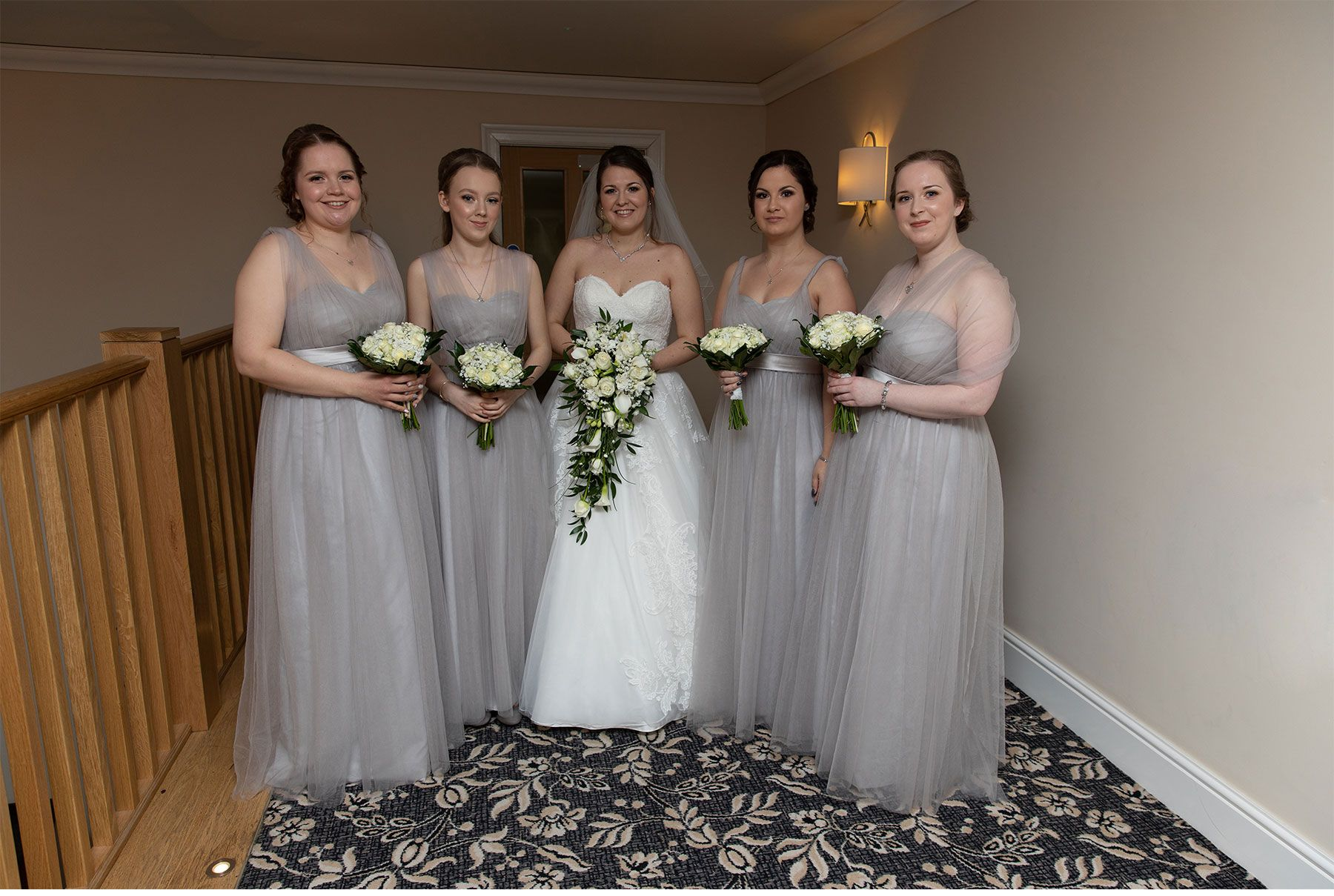 Bride and bridesmaids ready to go down stairs